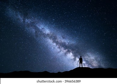 Landscape with Milky Way. Night sky with stars and silhouette of a standing happy man on the hill.