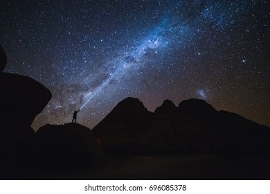 Landscape with Milky Way. Night sky with stars and silhouette of a standing man on the mountain.