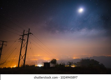 Landscape of milky way on top mountain with electric poleand the city below.