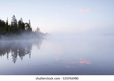 landscape misty morning on the lake in Canada, the surface of the water and morning summer mist, beautiful landscape wallpaper