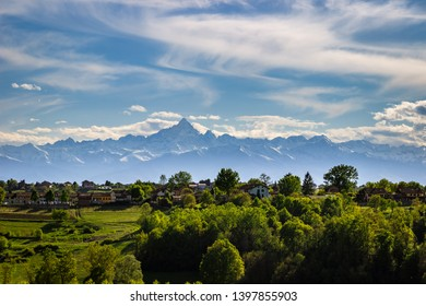 Landscape of the Monferrato hills with the Alps as a background. Telephoto from Don Bosco Hill in the province of Asti, Italy. You can see the Monviso peak known for its pyramid-like shape