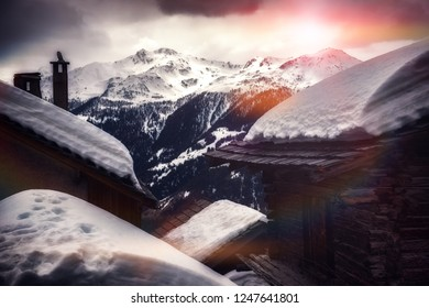Landscape with mountain peaks and chalet roof tops covered by snow. Nature background