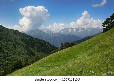 Landscape of mountain peaks in snow and green hills, blue sky and huge white clouds, Caucasian mountains, Karachaevo-Cherkessia, Russia