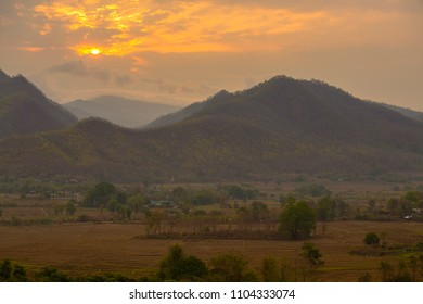 Landscape of mountain views and sunrise at viewpoint in Pai, Chiang Mai, Thailand. Amazing view of field, trees and village, with sunrise in the mountains on the background, Pai, Northern Thailand