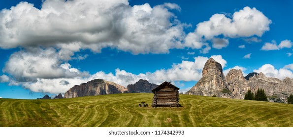 Landscape of mountains of Alta Badia in the Dolomites in summer season with green meadow in foreground, Italy