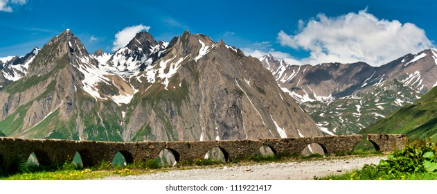 landscape of mountains of Formazza Valley in a clear day of spring with wall in the foreground with blur and blue sky and clouds in background, piedmont - Italy