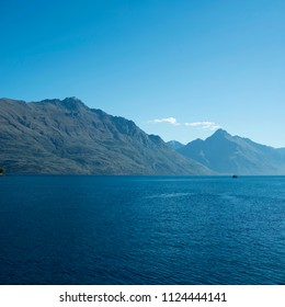 Landscape of mountains in front of a lake. Daytime scene, blue and clear sky. New Zealand.