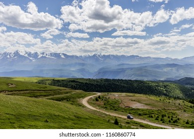 landscape of mountains with a passing car on the road