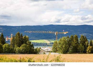Landscape with mountains, river and construction crane in Lillehammer, Norway.