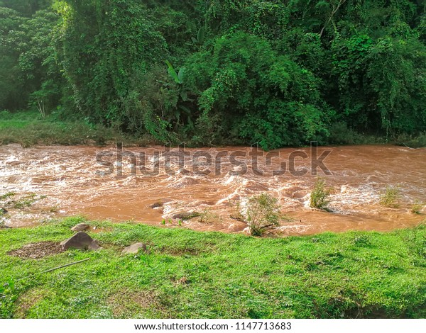 landscape with mountains,rain forest and a brown river in front.beautiful big green valleys at Nan province in Thailand.