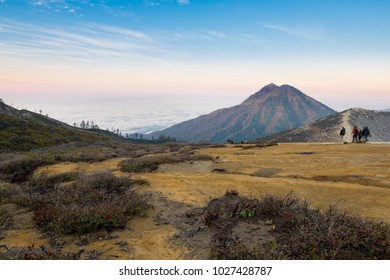 Landscape of Mt. Ijen with tourists trekking along the rim of crater at sunrise, Indonesia