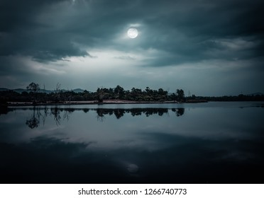 Landscape of night sky. Beautiful bright full moon and cloudy above silhouettes of trees, river area. Serenity nature background.