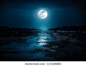 Landscape of night sky with many stars. Beautiful bright full moon above along deep canal in rural area. Outdoor with moonlight. Serenity nature background. The moon taken with my camera.