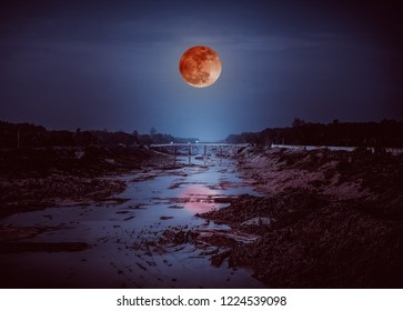Landscape of night sky with many stars. Beautiful blood moon above along deep canal in rural area. Outdoor with moonlight. Serenity nature background. The moon taken with my camera.