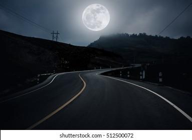Landschaft der Nachtzeit mit kurviger Straße im Wald im Nationalpark. Gebirgskurvenstraße vorbei, nachts im Freien. Dunkler Ton. Der Mond mit meiner eigenen Kamera aufgenommen, keine NASA-Bilder verwendet.