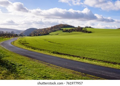 Landscape in north of France, Ardennes region, France. Black asphalt street in foreground with green grass field and hill with forest on top. Autumn fall season.
