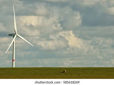 Landscape of north Frisia showing a wind turbine standing on a dike and the cloudy sky in the background.
