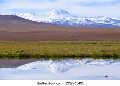 The landscape of northern Chile with the Andes Mountains and volcanoes that are reflected in the lagoons, Atacama Desert, Chile