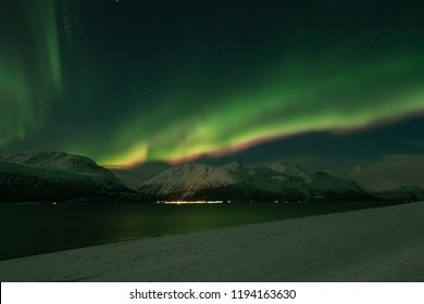 Landscape with northern lights over the Norway fjord in winter.