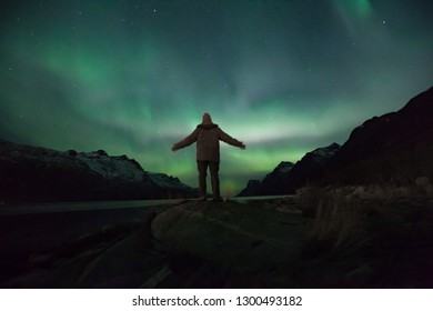 Landscape in Norway with northern lights in green, blue violet and person in front of it