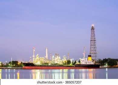 landscape of Oil refinery plant along river with tanker at dusk