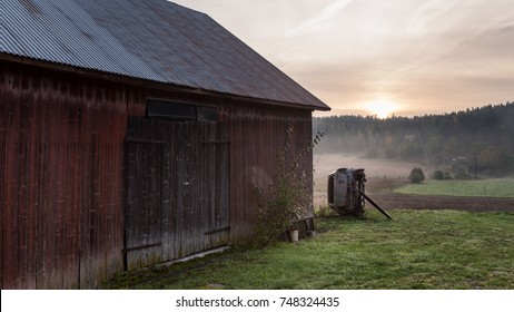 Landscape of old barn and rusty car in countryside.