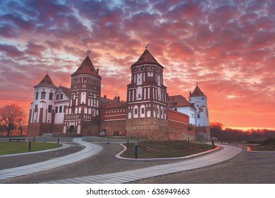 Landscape of an old castle against a colorful sky on a beautiful dawn. Mir Castle in Belarus at dawn with a colorful sky. Beautiful scenery.