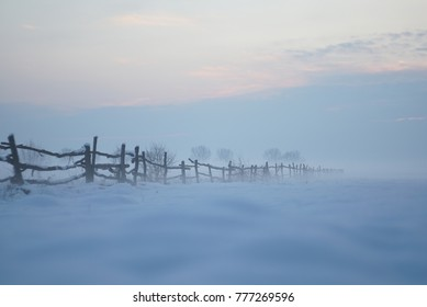 The landscape of an old fence against the background of a misty winter day