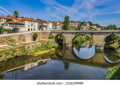 Landscape with old stone bridge over a river and houses in Coja village, Portugal