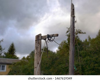 Landscape with old wooden electric pole and sagged wires