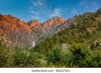 landscape on the background of blue sky. The tops of the mountains are illuminated in pink and surrounded by greenery.  Uzbekistan. Chimgan.