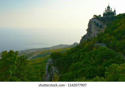 Landscape on Black Sea coast in Crimea. Church Voskreseniya Khristova at top of rocky cliff the Red Rock against light sky and sea in September evening. Green forest and the Foros village on coast.