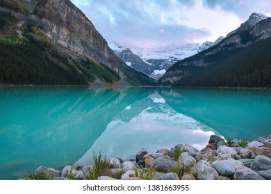 landscape on a glacier turquoise lake, mountains reflected on the calm blue water by a peaceful, beautiful sunny day in Canada at spring, snow in the background, rocky shore on the foreground