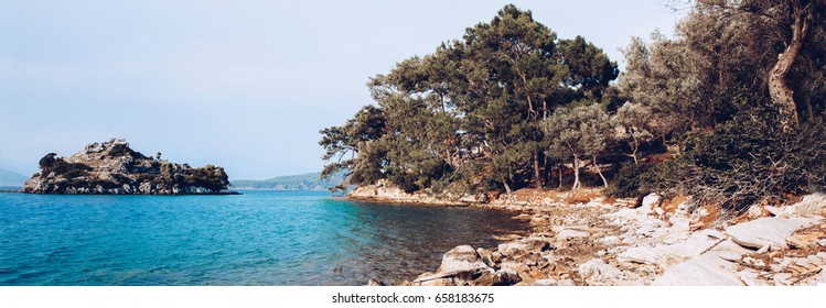 landscape on mediterranean Sea view with rock and stone beach. Paradise place on Dalaman Turkey island. Blue transparent water. Tourism. Travel panoramic photo for web site