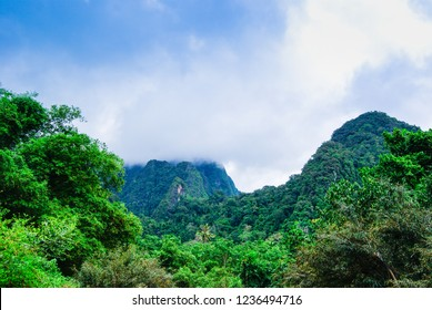 Landscape on a mountain range in a wildlife reserve in Thailand. green trees, mountains in the clouds. vacation in a warm country.