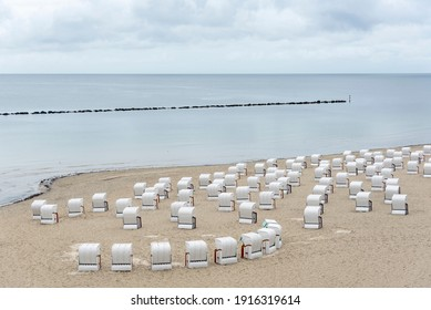 Landscape on Rugen island with the empty beach and the Baltic Sea. Beach in the city of Sassnitz, Germany filled with hooded beach chairs.