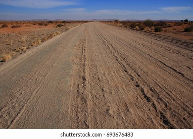 Landscape with open dirt road leading to the far horizon in landscape format with copy space