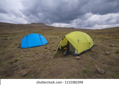 A landscape orientated photograph of a blue and yellow hiking tent with an open door under a stormy cloudy sky on top of a mountain, at the uKhahlamba Drakensberg escarpment Park in South Africa