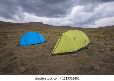 A landscape orientated photograph of a blue and yellow hiking tent with a closed door under a stormy cloudy sky on top of a mountain, at the uKhahlamba Drakensberg escarpment Park in South Africa