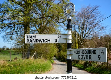 Landscape orientation of amusing funny fingerpost road sign post with village of Ham and town of Sandwich and also Northbourne and Dover in Kent, England