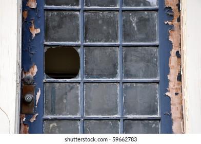 Landscape orientation close up of broken window pane in an old door with peeling paint.