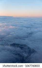 Landscape over the clouds. Fluffy clouds with pink tops over the snow-covered ground under the blue sky. A view from an airplane.