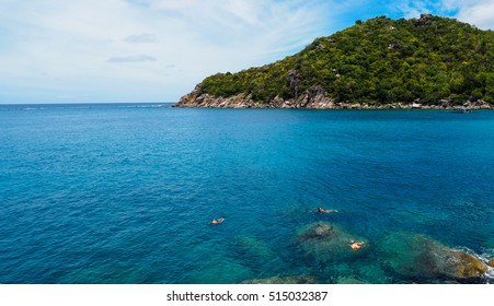 Landscape over and under water surface, tropical island shore with natural trench into the fore reef split by depth with group of snorkeling