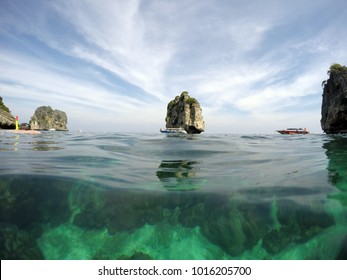 Landscape over and underwater surface. Sky with clouds, tropical cliffs and coral reef split by waterline. Koh Haa, Krabi, Koh Lanta, Thailand