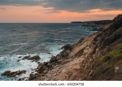 Landscape of the Pacific Ocean by a cliff at sunset located in Huatulco, Oaxaca state, Mexico.