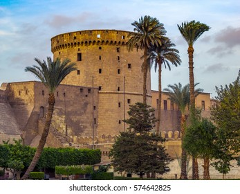 Landscape with palms and Citadel of Saladin in Cairo - ancient architecture and historical landmarks of Egypt. Traditional medieval fortress in eastern style, popular tourist place of travel.