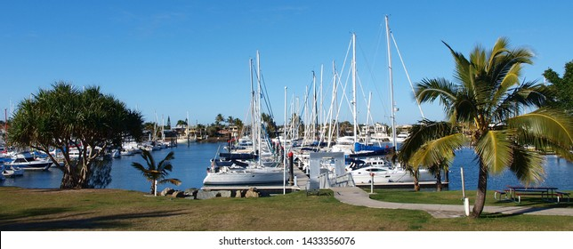 Landscape panorama with boats berthed at a tropical waterfront marina including Palm trees and blue sky backdrop. Safe haven for sailing and cruising vessels. Mooloolaba, Queensland Australia.