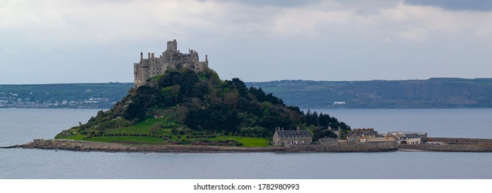 Landscape panorama of the Mouth's bay featuring St Michael's Mount in the middle. This is a tidal island connected to mainland through a man made granite causeway. It has a fortress and unique geology