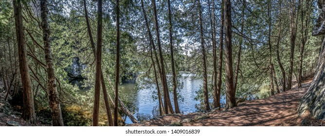 Landscape panorama of a trail through northern woods along the edge of a lake