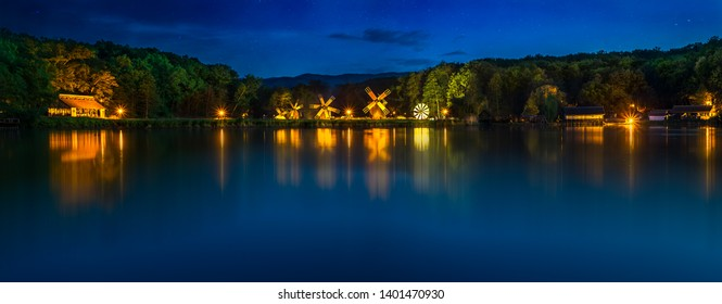 Landscape panorama with windmills at the blue hour in White Night of the Museums 2019. Dumbrava lake, Astra Museum of Traditional Folk Civilization, Sibiu city, Romania